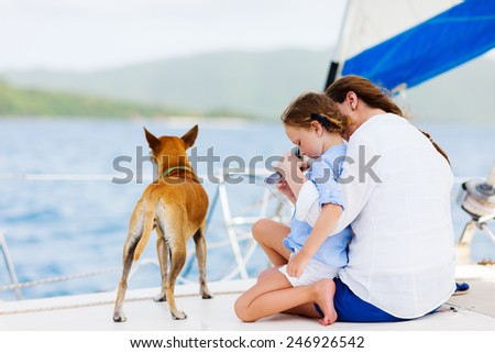 Back view of mother, daughter and their pet dog sailing on a luxury yacht or catamaran boat - stock photo