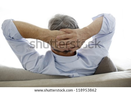 Back view of old man relaxing in sofa