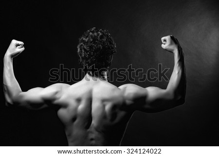 Back view of one handsome sexy strong muscular young man training with bare shoulders and curly hair standing with raised hands indoor on studio background black and white, horizontal picture - stock photo