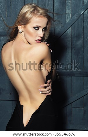 Back view of one sexual attractive slender blonde woman with flexible straight body undressing standing in black dress in studio on wooden wall background, vertical picture - stock photo