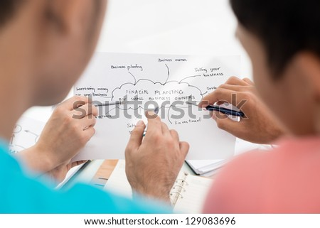Back view of people working with financial plan - stock photo