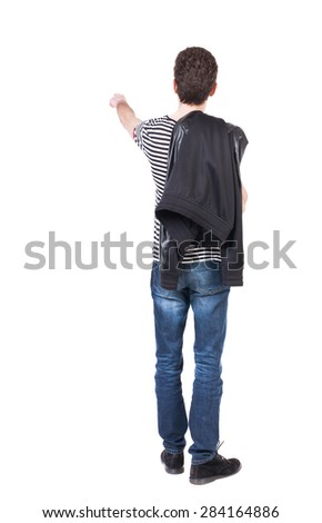 Back view of pointing man in winter jacket  looking up.   Standing young guy in parka.  Putting his jacket on his right shoulder guy shows finger of the other hand. - stock photo