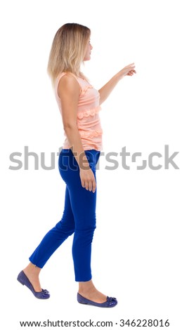 back view of pointing walking  woman. going girl pointing.  backside view of person.  . Isolated over white background. blonde in blue pants is holding up his left hand to the right. - stock photo