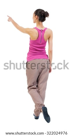 Back view of  pointing woman. beautiful girl. Rear view people collection.  backside view of person.  Isolated over white background. tanned girl shows her legs crossed ahead. - stock photo