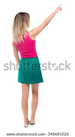 Back view of  pointing woman. beautiful girl. Rear view people collection.  backside view of person.  Isolated over white background.  Girl in a green skirt shows the right hand to the sky. - stock photo