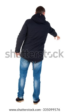 Back view of  pointing young men in parka. Young guy  gesture. Rear view people collection. backside view of person.  Isolated over white background. Man in warm jacket with his left hand points down  - stock photo