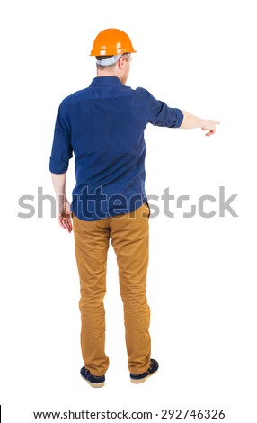 Back view of  pointing young men in  shirt and helmet. Young guy  gesture. Rear view people collection.   Isolated over white background. Young engineer in a blue shirt points to the work front  - stock photo