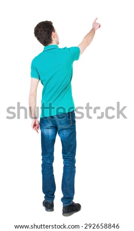 Back view of  pointing young men in  shirt and jeans. Young guy  gesture. Rear view people collection.   Isolated over white background. guy in a stylish T-shirt shows a finger of his right hand up  - stock photo