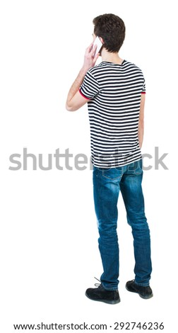 Back view of  pointing young men talking on cell phone. Young guy  gesture. Rear view people collection. Isolated over white background. The guy in the striped shirt and white talking on a cell phone  - stock photo