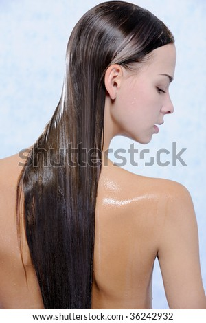 Back view of pretty young female with wet long hairs - stock photo