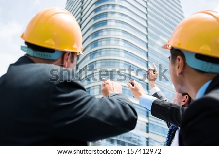 Back view of professional engineers pointing at the modern building on the foreground - stock photo