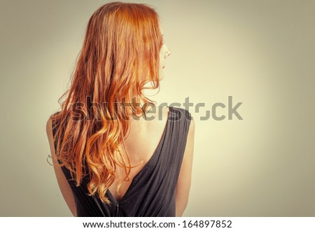 Back view of Red curly long hair of Beautiful Woman with a lot of copyspace - stock photo