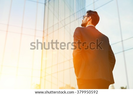 Back view of rich businessman with hands in pockets looking on his skyscraper building while standing outside, young confident male manager dreaming about growth his career during work break outdoors - stock photo