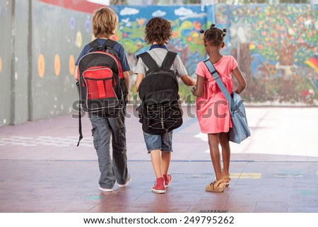 Back view of school mates walking on the schoolyard. Multi ethnic classroom. - stock photo