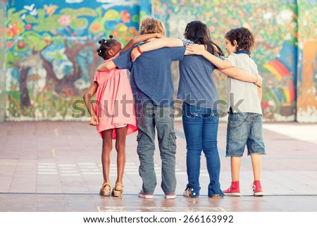 Back view of schoolchildren embracing at primary school. - stock photo