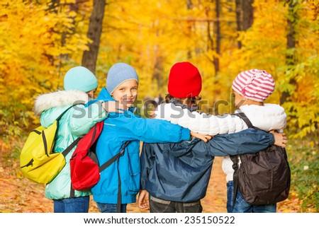 Back view of schoolchildren row standing close - stock photo