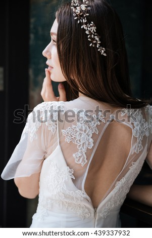 Back view of sensual young bride in white dress and wreath - stock photo