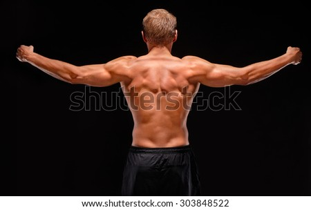 Back view of sexy male shirtless muscular sportsman with raised hands demonstrating back, biceps, triceps, shoulder muscles. Isolated on black background. Dressed in black shorts - stock photo