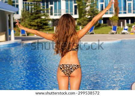 Back view of sexy woman with tanned skin is swimming in pool, summer time