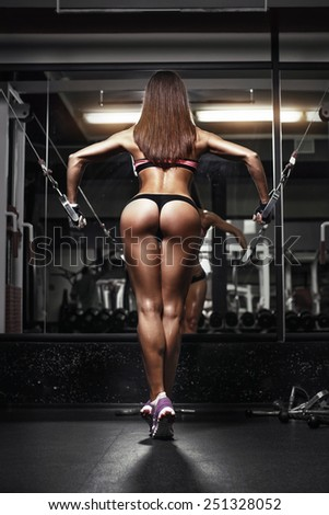 back view of sexy young brunette woman workout in the gym. Fitness girl in gym in a blue sport wear - stock photo