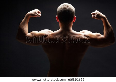 Back view of shirtless man demonstrating his strong arms - stock photo