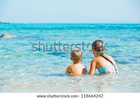 Back view of sister and brother playing and swimming in the transparent sea - stock photo