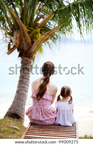 Back view of sitting mother and daughter sitting under palm