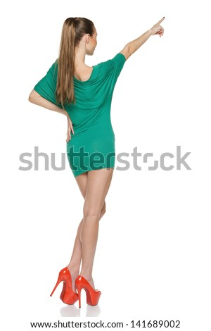 Back view of slim young female wearing green mini dress in full length pointing up, against white background - stock photo