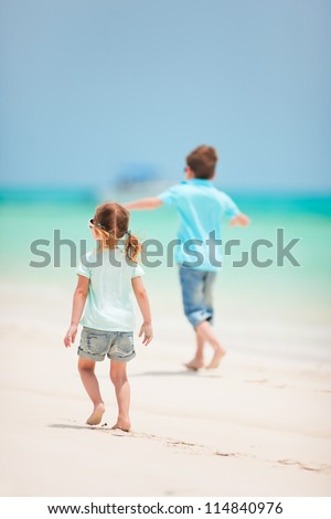 Back view of small kids running at tropical beach