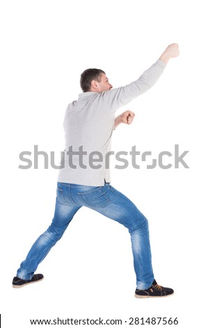 back view of standing man pulling a rope from the top or cling to something. guy watching. Rear view people collection.  backside view of person.  Isolated over white background. legs apart man pulls - stock photo