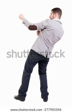 back view of standing man pulling a rope from the top or cling to something.  Rear view people collection.  backside view of person. - stock photo