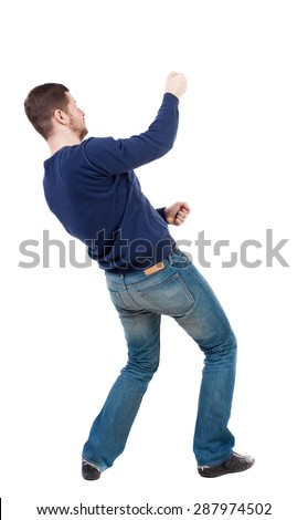 back view of standing man pulling rope from top or cling to something. guy watching. Rear view people collection. Isolated over white background. Man in jeans and blue sweater pulls the rope on top - stock photo