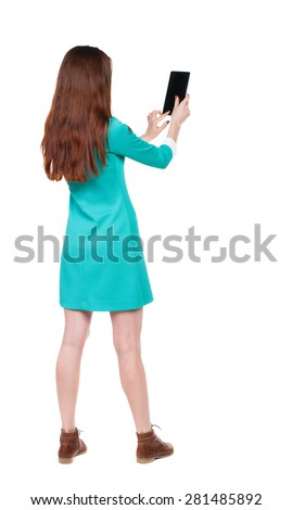back view of standing young beautiful  girl with tablet computer in hands of.  backside view of person.  Isolated over white background. girl in blue dress with brown shoes photographed using  tablet. - stock photo
