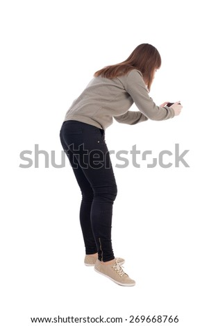 back view of standing young beautiful  woman and using a mobile phone. girl  watching. Rear view people collection.  backside view of person.  Isolated over white background. - stock photo
