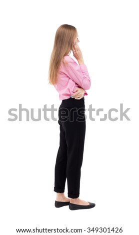 back view of standing young beautiful  woman.  girl  watching. Rear view people collection.  backside view of person.  girl office worker in black trousers stands sideways and looks thoughtfully left - stock photo