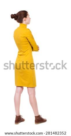 back view of standing young beautiful  woman in dress.  girl  watching. Rear view people collection.  Isolated over white background. Girl in mustard strict dress stands sideways and looks right. - stock photo