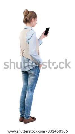 back view of standing young beautiful  woman  in vest and using a mobile phone. girl  watching. Rear view people collection.  backside view of person.  Isolated over white background.  - stock photo
