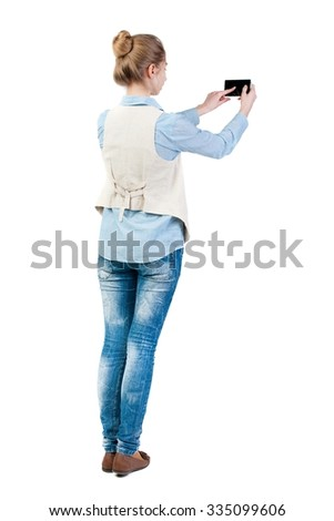 back view of standing young beautiful  woman  in vest and using a mobile phone. girl  watching. Rear view people collection.  backside view of person.  - stock photo