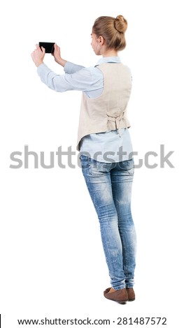 back view of standing young beautiful  woman  in vest and using a mobile phone. Rear view people collection.  backside view of person.  Isolated over white background. Girl doing selfie on your phone. - stock photo