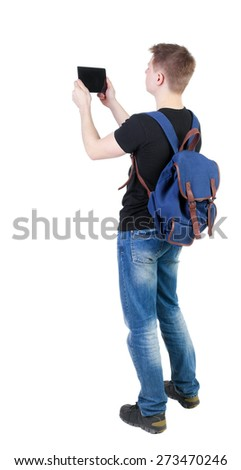 Back view of standing young man with tablet computer and backpack. Rear view people collection.  backside view of person.  Isolated over white background.  - stock photo