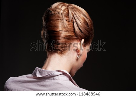 back view of stylish woman with hairdo over black background - stock photo