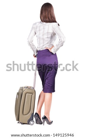 Back view of stylishly dressed brunette business woman with suitcase looking up. Standing young girl.   Isolated over white background. languid girl in heels looks into the distance - stock photo