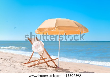 Back View Of Sun Parasol, Woman's Hat and Deckchair On Sandy Beach Vacation