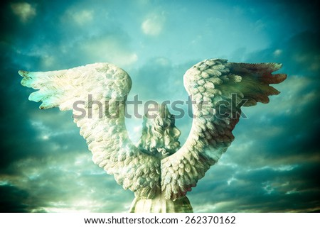 back view of the statue of an angel composite with mystical sky - stock photo