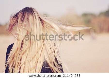 Back view of the young female with beautiful blond straight long hairs in motion - stock photo