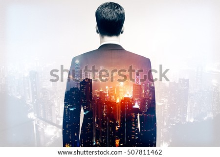 Back view of thoughtful businessman in suit on night city background. Research concept. Double exposure