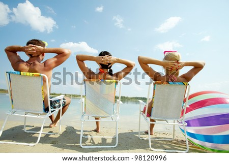 Back view of three friends resting in chairs on the beach - stock photo