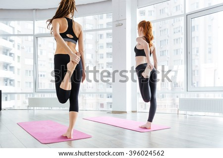 Back view of two attractive young women standing and stretching legs on pink yoga mat - stock photo
