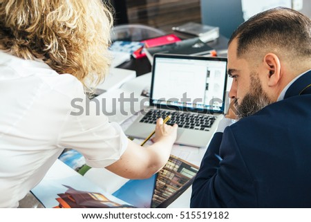 Back view of unrecognizable female designer showing illustrated book with designs to man