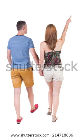 Back view of walking young couple (man and woman) pointing. going tourists in shorts considering attractions. Rear view people collection. backside view of person. Isolated over white background - stock photo